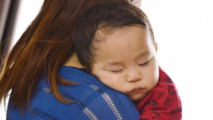 熟睡中の赤ちゃんを抱っこするママ