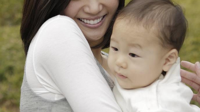 遠くを見つめる赤ちゃんを抱きしめるママ