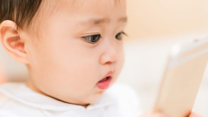スマートフォンを見つめる赤ちゃん