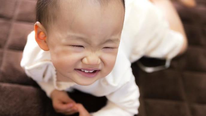 うつぶせでママに視線を送り笑顔になる赤ちゃん