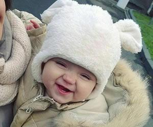 白いもこもこ帽子にご満悦な赤ちゃん