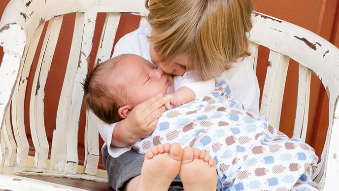 新生児の赤ちゃんを抱いて可愛がる兄弟