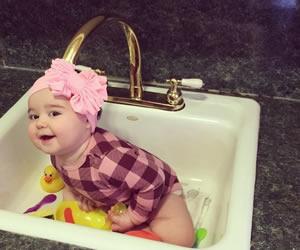 ピンクのヘアバンドとチェックの上着が似合う赤ちゃん