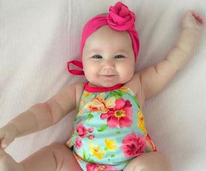 ハイビスカスのロンパースを着て喜ぶ赤ちゃん