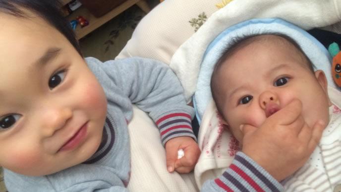 兄に顔をつままれる赤ちゃん