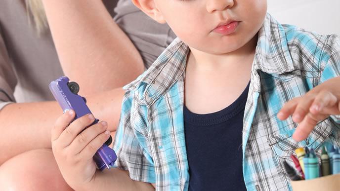 おおもちゃで遊ぶ男の子とそれを見守るベビーシッター