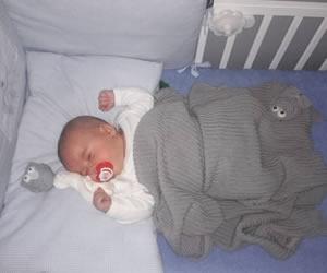 おしゃぶりをしながら寝るバンザイ中の新生児