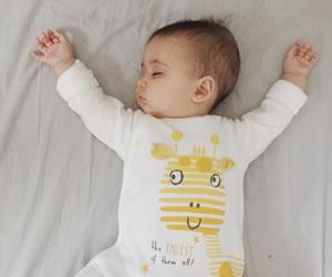 キレイなバンザイをしながら眠りにつく赤ちゃんの横顔