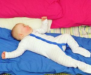 体操着のようなカバーオールで寝る赤ちゃん