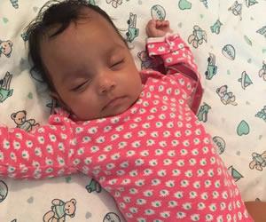赤のロンパースを着こなすバンザイ寝で熟睡する赤ちゃん