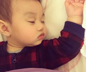 横向きの寝顔とバンザイするむちむちの手