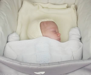 白い手袋に覆われたバンザイをして寝る赤ちゃん