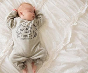 柔らかい腕を折り曲げ熟睡する赤ちゃん