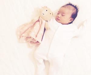 全身を覆うカバーオールに包まれ熟睡中の赤ちゃん