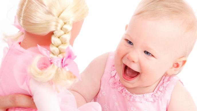 ペアルックの人形に興味がある女の子の赤ちゃん