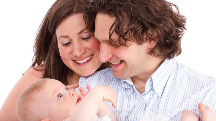 ハイハイが待ち遠しいママとパパに抱えられる赤ちゃん