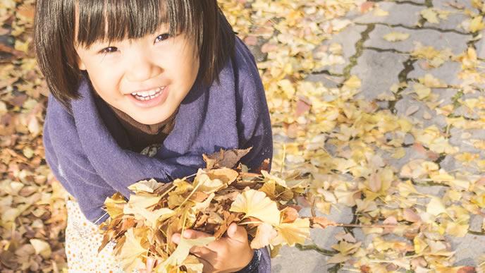 落ち葉でママと一緒に遊ぶ子供