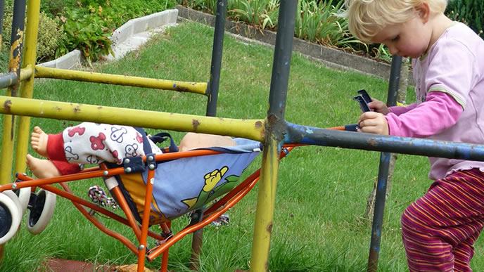 金属製の安全なベビーカーに乗せられた赤ちゃんの人形