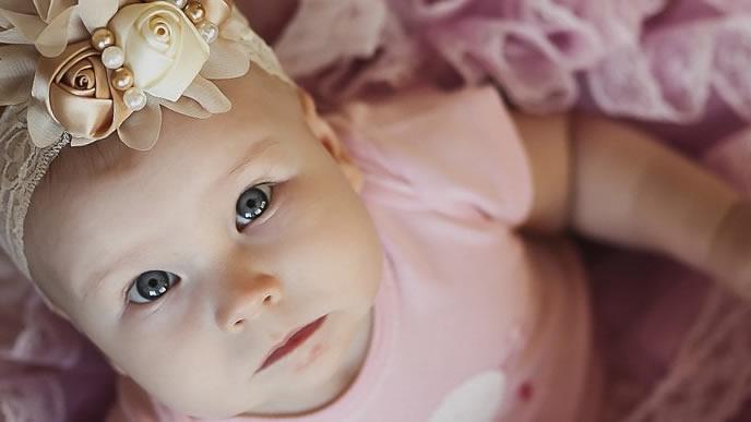 ママの顔を見上げるヘアバンドが可愛い赤ちゃん