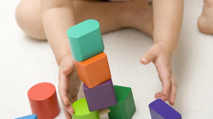 積み木のおもちゃで1人遊び中の赤ちゃん