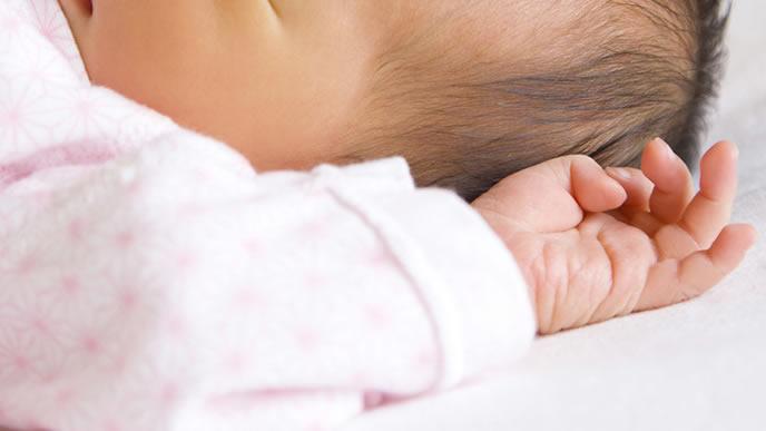 モロー反射で手をピクっとさせる赤ちゃん
