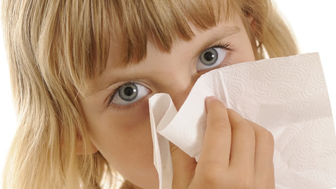 鼻水を厚手のティッシュでかむ女の子