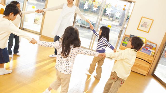 幼稚園で輪になって遊ぶ子供達