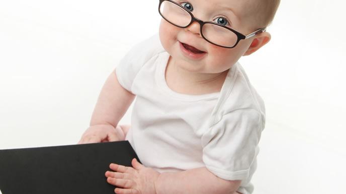 本を開くメガネをかけた赤ちゃん