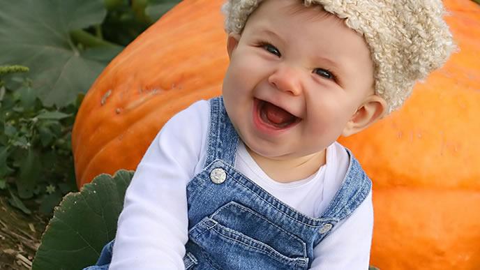 外出時はお気に入りの帽子をかぶる笑顔の赤ちゃん