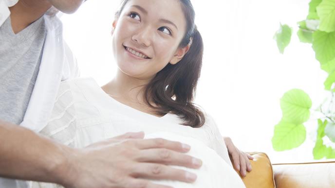 夫と一緒にお腹の中の赤ちゃんを撫でる夫婦