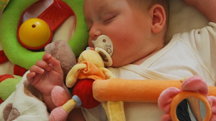 寝ている時もお気に入りのおしゃぶりを離さない赤ちゃん