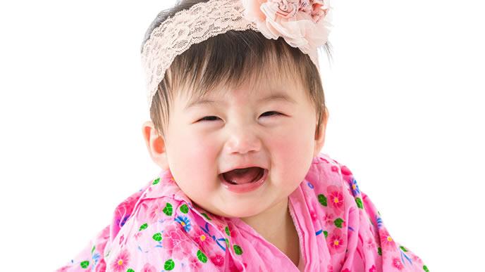 お宮参りの衣装を着て喜ぶ赤ちゃん