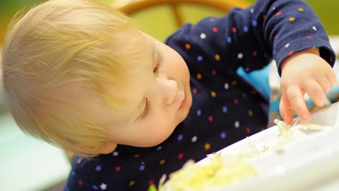 手づかみで離乳食を食べる金髪の赤ちゃん