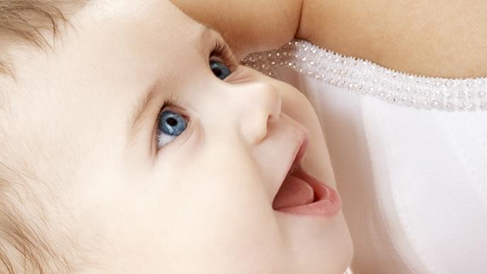 ママの顔を見つめて笑顔になる生後間もない赤ちゃん