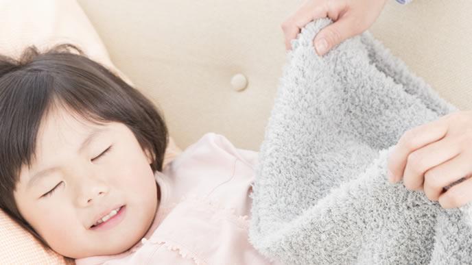 腹痛に苦しむ女の子に優しく毛布をかけるママ