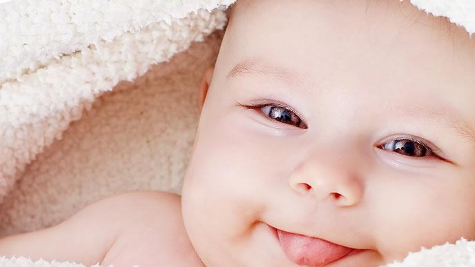 愛くるしい笑顔が可愛いタオルに包まれた赤ちゃん