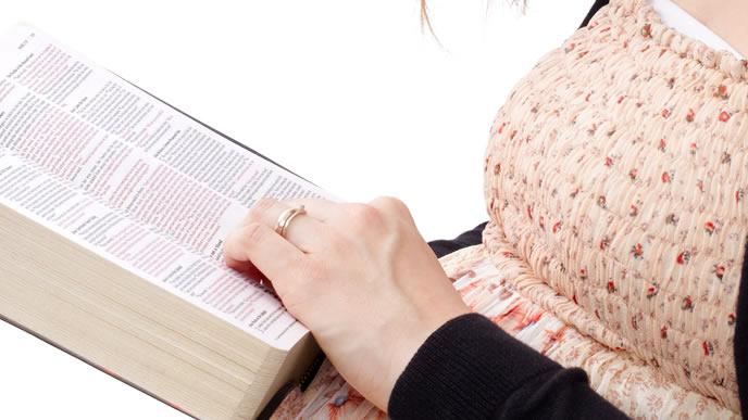微弱陣痛の危険性と対処法を本で調べている妊婦さん