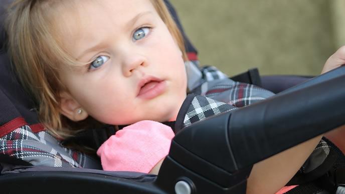 ベビーカーに乗せられ外出中の幼児