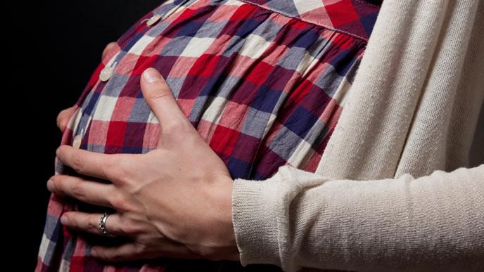 連続した前駆陣痛に耐える出産間近の臨月の妊婦さん
