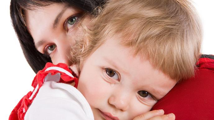 便秘が辛い赤ちゃんを慰めるママ