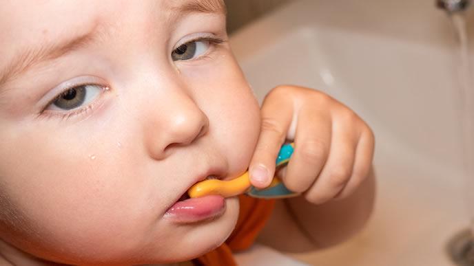 今にも眠気に負けそうな歯磨き中の赤ちゃん