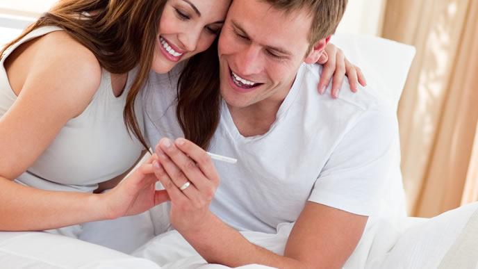 妊娠検査薬の陰性が陽性に変わり喜ぶカップル