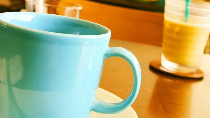 のどが乾きいきつけのカフェでお茶をする女性