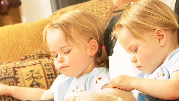 双子の赤ちゃんに絵本を読み聞かせる母親