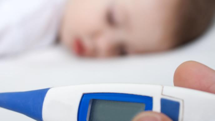 体温計で赤ちゃんの熱をチェックするママ