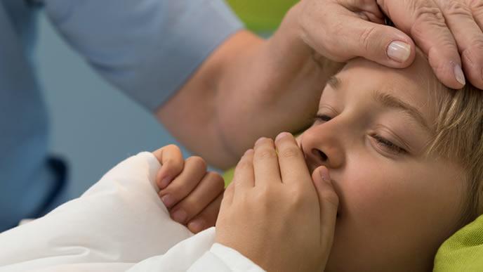 子供の熱が心配になりベッドで介護するママ