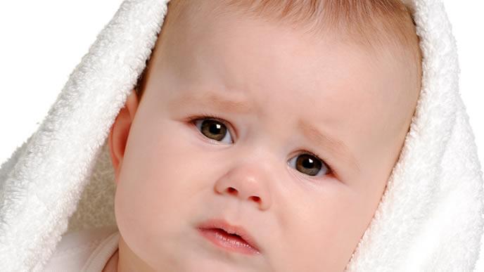鼻血を出しそうな悲しい表情の赤ちゃん