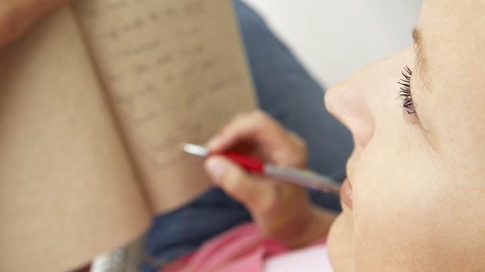 危険なおりものをノートにメモする妊婦さん