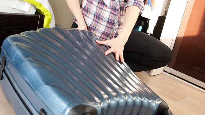 長期旅行のため大きめのバッグに荷物を詰め込む女性