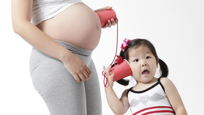 お母さんの胎動を聞く女の子